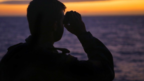 "A photo taken on April 7, 2014 and released by Australian Defence on April 11 shows Able Seaman Boatswains Mate Rothnie Marshall looking for any sign for the missing Malaysia Airways Flight MH370. Australian Prime Minister Tony Abbott said he is ""very confident"" that signals detected in the search for Flight MH370 are from the aircraft's black box, whose batteries are waning fast more than a month after the plane vanished."