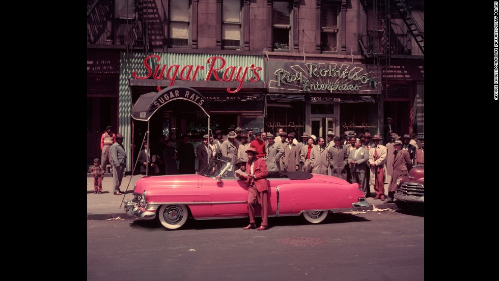 Robinson became known for his flashy lifestyle, including a legendary pink Cadillac.  He is seen here in Harlem in 1950 outside his club, Sugar Ray's.