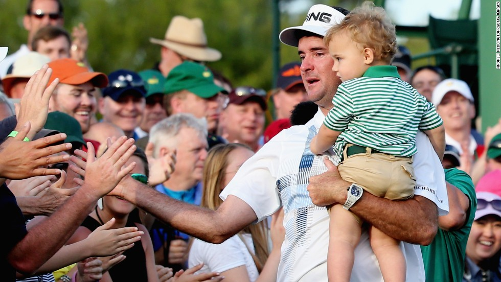 An emotional Watson holds his son, Caleb, as he celebrates with fans by the 18th green at Augusta.