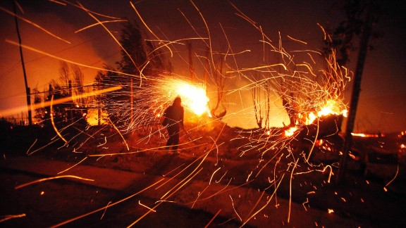 A person tries to extinguish flames as sparks fly.