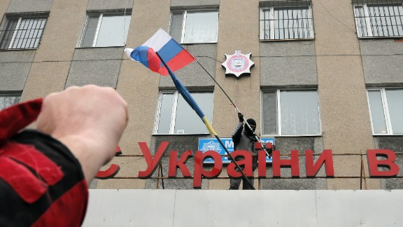 "A pro-Russian man places a Russian flag over a police station during its mass storming in the eastern Ukrainian town of Horlivka on Monday, April 14, 2014.  The text reads: Ukrainian police station in Horlivka"". Several government buildings has fallen to mobs of Moscow loyalists in recent days as unrest spreads across the east of the country.  (AP Photo/Efrem Lukatsky)"