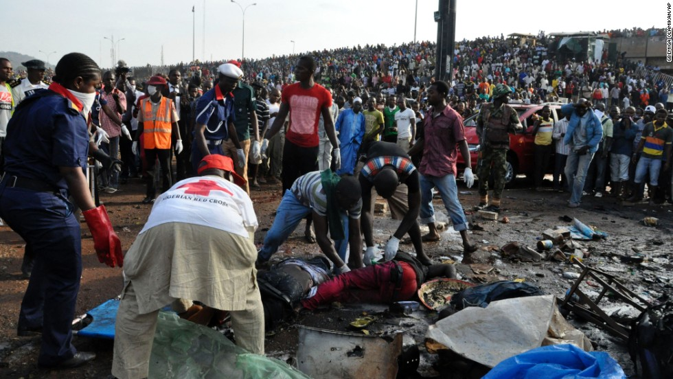 Rescue workers collect the bodies of victims as people gather at the site of the blast on April 14.