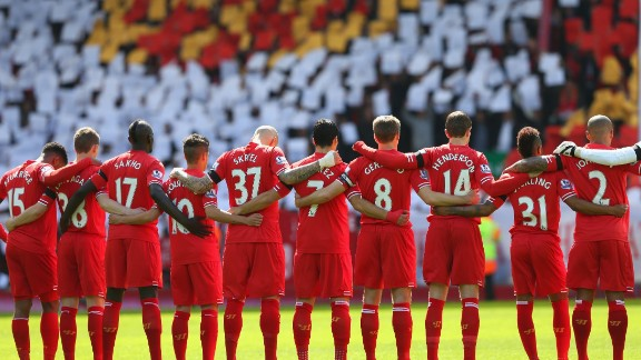 The Liverpool players link arms as they join a silence for the victims in 2014.