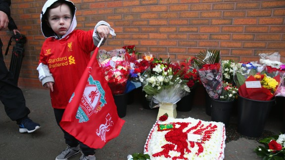 A young Liverpool fan stands next to floral tributes laid in memory of the victims on the 25th anniversary.