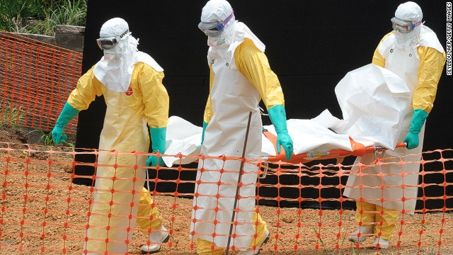 Staff of the 'Doctors without Borders' ('Medecin sans frontieres') medical aid organisation carry the body of a person killed by viral haemorrhagic fever, at a center for victims of the Ebola virus in Guekedou, on April 1, 2014.
