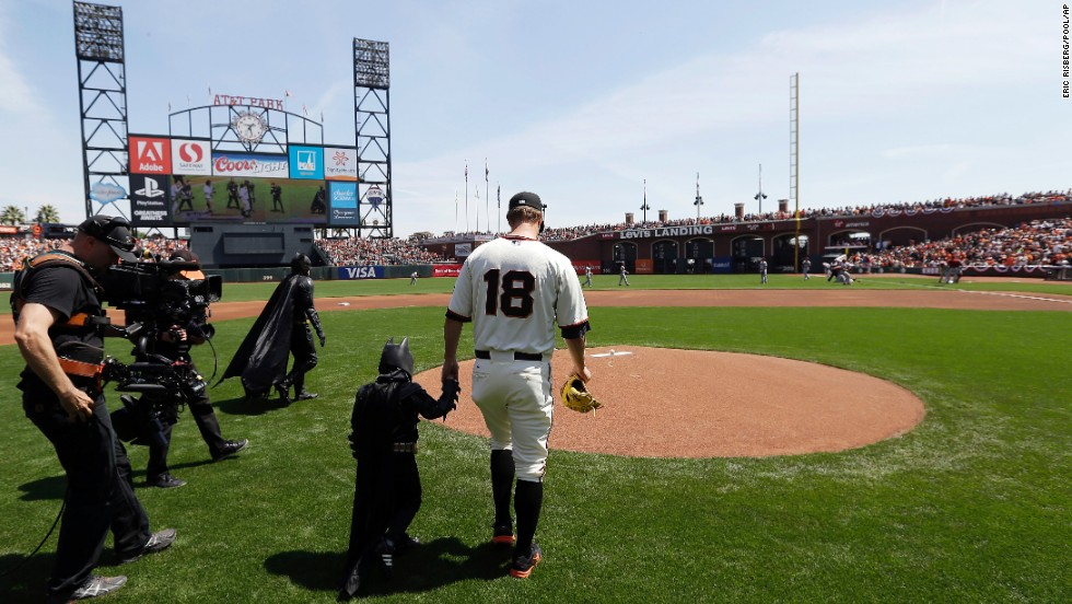 "Miles Scott, dressed as Batkid, walks to the mound with San Francisco Giants pitcher Matt Cain before <a href=""http://www.cnn.com/2014/04/09/us/gallery/batkid-throws-first-pitch/index.html"">throwing out the ceremonial first pitch</a> at the Giants' home opener on Tuesday, April 8. Miles, a 5-year-old who has been fighting leukemia since he was a baby, made headlines in November when, through the Make-A-Wish Foundation, he became Batman for a day and got to ""save"" the city."