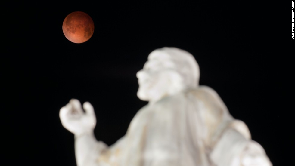 "A ""blood moon"" rises over the El Salvador del Mundo monument in San Salvador early Tuesday, April 15, 2014, as a total lunar eclipse attracts sky gazers across the Americas. In a total lunar eclipse, the full moon turns a coppery red as it passes into Earth's shadow. ""It's like seeing all the sunsets on Earth projected on the moon at once,"" says Indra Petersons of CNN's ""New Day."""