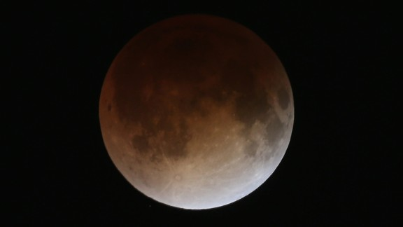 The red hue is caused by refracted sunlight in the Earth's atmosphere, which bounces off the moon while in shadow. The entire reddening process takes about an hour.