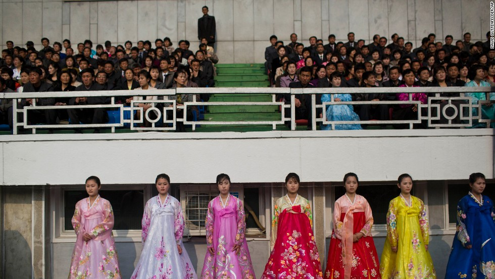 North Korean women in traditional dresses stand next to the running track inside Kim Il Sung Stadium.