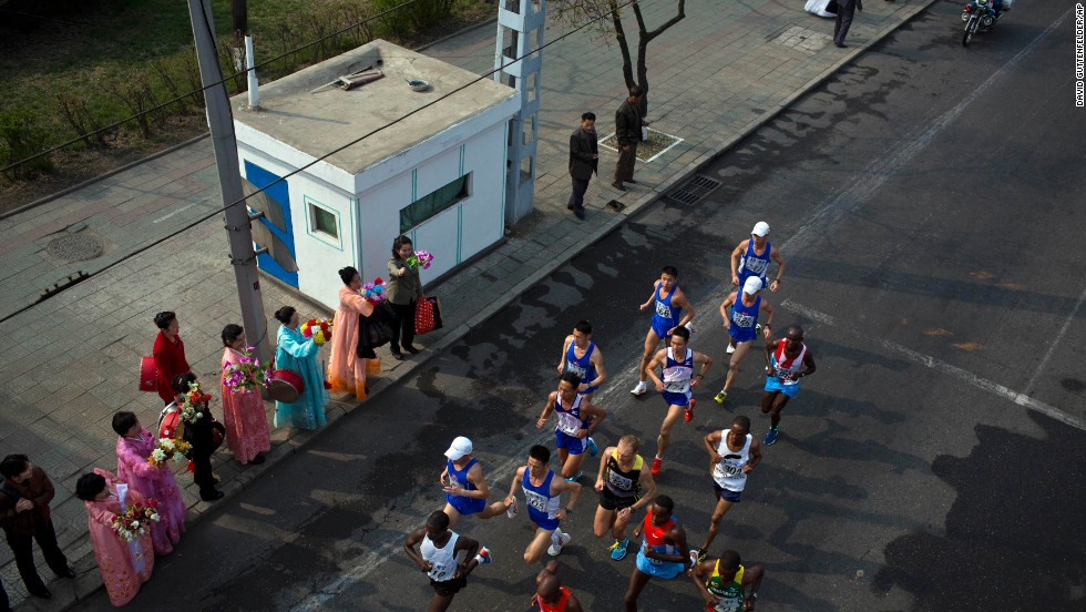 The lead pack of runners are cheered on by spectators at the roadside in central Pyongyang.