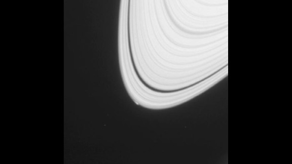A small, bright blip can be seen on the outermost edge of Saturn