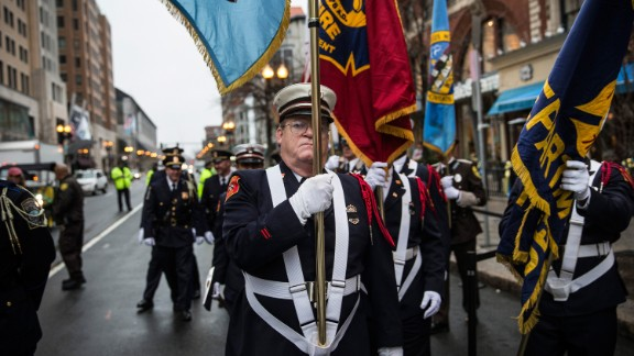 Members of the Boston Police Department, the Boston Fire Department and the Massachusetts State Police march prior to Tuesday's wreath-laying ceremony.