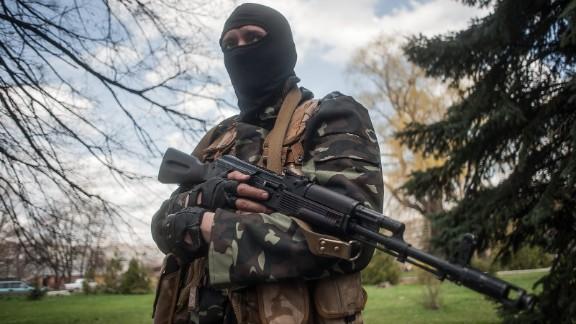 A masked gunman stands guard near tanks in Slaviansk, Ukraine, on Wednesday, April 16.