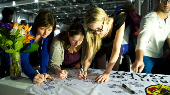 University of Calgary students and staff sign condolences on a banner during a memorial service for victims.
