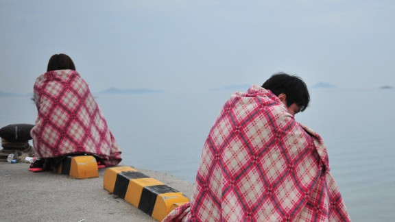 Caption:South Korean relatives wait for missing people at a harbor in Jindo on April 16, 2014 as South Korean rescue teams, including elite navy SEAL divers, raced to find up to 293 people missing from a capsized ferry carrying 459 passengers and crew -- mostly high school students bound for a holiday island. Two people -- a male student and a female crew member -- were confirmed dead as the vessel sank 20 kilometres (13 miles) off the southern island of Byungpoong. AFP PHOTO / JUNG YEON-JE (Photo credit should read JUNG YEON-JE/AFP/Getty Images)