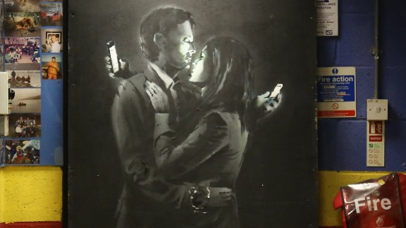 "A Banksy work appears at a youth center in Bristol, England, in April 2014. Called ""Mobile Lovers,"" it features a couple embracing while checking their cell phones. Members of the youth center took down the piece from a wall on a Bristol street and replaced it with a note saying the work was being held at the club ""to prevent vandalism or damage being done."" The discovery came shortly after another image believed to be by Banksy surfaced in Cheltenham, England."