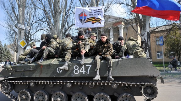 Men wearing military fatigues sit by a Russian flag and a white flag reading 'People's volunteer corps of Donetsk' as they ride on an armoured personnel carrier (APC) in the eastern Ukrainian city of Slavyansk on April 16, 2014.