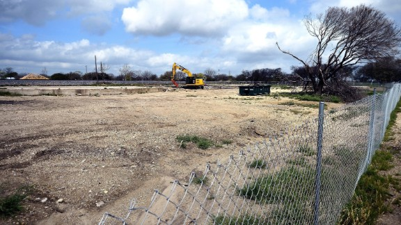 A fence surrounds the barren site of West Fertilizer Co. Twelve months later, authorities haven