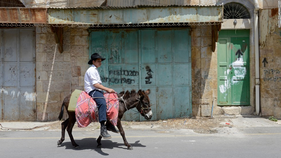 An Israeli boy rides a donkey past shuttered Palestinian shops near the Cave of Machpelah on April 16. Thousands of Israelis and tourists visit the contested town of Hebron to pray beside the graves of the patriarchs and matriarchs.