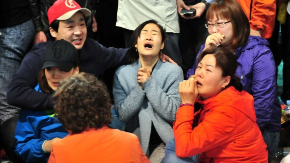 South Korean relatives of passengers on board a capsized ferry cry as they wait for news about their loved ones, at a gym in Jindo on April 17, 2014. The frantic search for nearly 300 people, most of them schoolchildren, missing after a South Korean ferry capsized extended into a second day on April 17, as distraught relatives maintained an agonising vigil on shore. AFP PHOTO / JUNG YEON-JE (Photo credit should read JUNG YEON-JE/AFP/Getty Images)