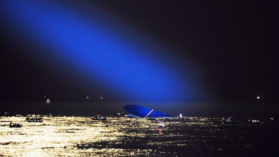 A searchlight illuminates the capsized ferry on Thursday, April 17.