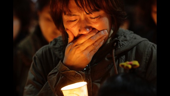 A woman cries during a candlelight vigil at Danwon High School in Ansan, South Korea, on April 17.