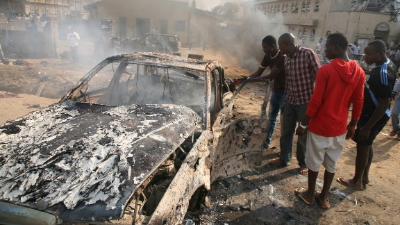 Men look at the wreckage of a car after a bomb blast at St. Theresa Catholic Church outside Abuja on December 25, 2011. A string of bombs struck churches in five Nigerian cities, leaving dozens dead and wounded on the Christmas holiday, authorities and witnesses said. Boko Haram