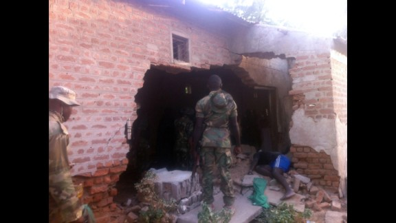 A soldier stands in front of a damaged wall and the body of a prison officer killed during an attack on a prison in the northeastern Nigerian town of Bama on May 7, 2013. Two soldiers were killed during coordinated attacks on multiple targets. Nigeria