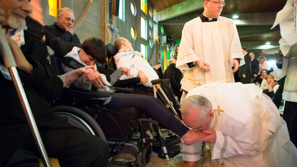 Pope Francis kisses the foot of a woman in Rome on Thursday, April 17.