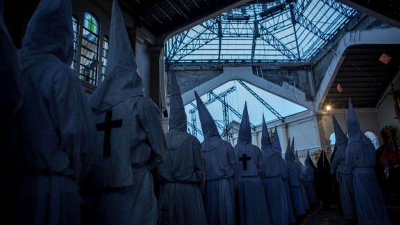 Penitents watch on from a damaged part of the Palo Cathedral during the Maundy Thursday Mass at Palo Cathedral in Palo, Leyte, Philippines, on April 17.