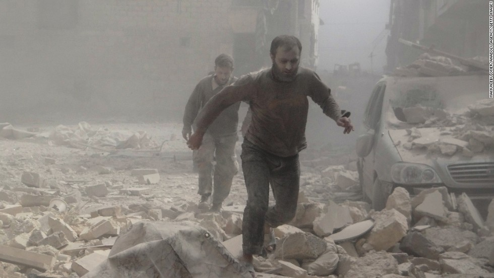 Syrians walk in rubble after clashes in Aleppo, Syria, on Saturday, April 12.