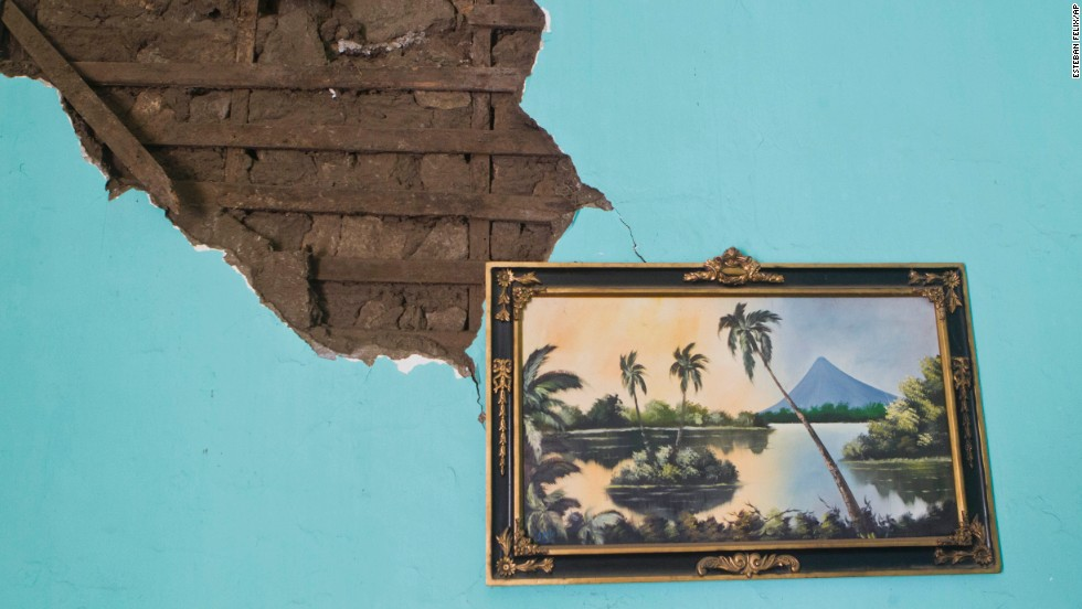 A painting of a Nicaraguan lake hangs from a damaged wall Friday, April 11, inside a home that was damaged a day earlier by an earthquake in Nagarote, Nicaragua.