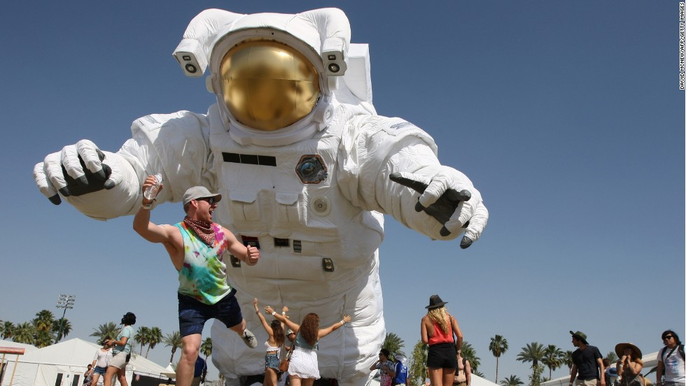 "A man poses for friends in front of a giant inflated astronaut Saturday, April 12, at the <a href=""http://www.cnn.com/2014/04/14/showbiz/gallery/coachella-festival/index.html"">Coachella Valley Music and Arts Festival</a> in Indio, California."