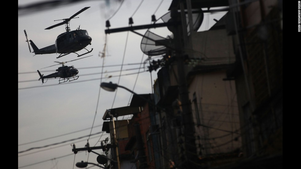 Police helicopters patrol over the favela.