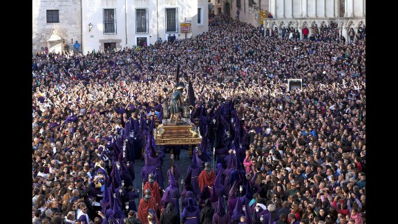 """Penitents, surrounded by several thousand people in Cuenca, Spain, carry a statue of Our Father Nazarene during the Good Friday procession """"Way of Calvary."""""""