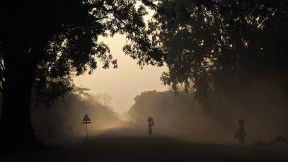 People are silhouetted at dawn on Thursday, February 20, as they walk on the main road to Cueibet, South Sudan.