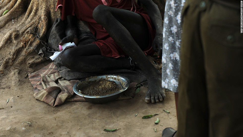 An inmate sits shackled to a tree Wednesday, February 19, in the courtyard of the central prison in Rumbek, South Sudan.