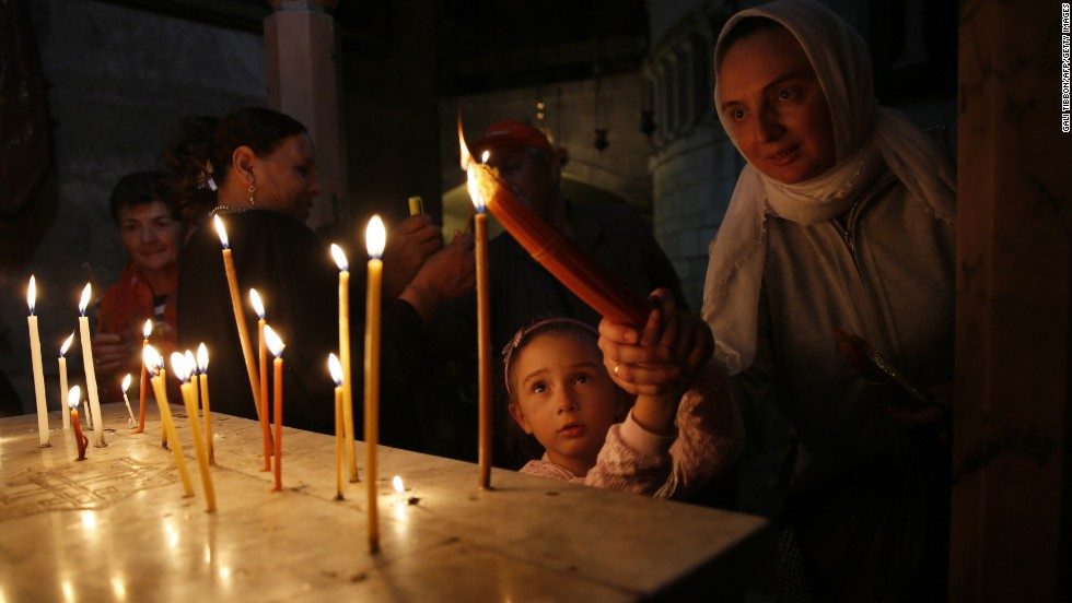 Christian worshippers light candles during Easter Sunday Mass in the Church of Holy Sepulchre in Jerusalem's Old City.