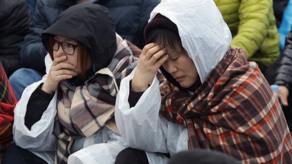 Caption:JINDO-GUN, SOUTH KOREA - APRIL 20: Relatives of missing passengers from the sunken ferry grieve as they try to go to the presidential house on April 20, 2014 in Jindo-gun, South Korea. At least forty six people are reported dead, with 256 still missing. The ferry identified as the Sewol was carrying about 470 passengers, including the students and teachers, traveling to Jeju Island. (Photo by Chung Sung-Jun/Getty Images)