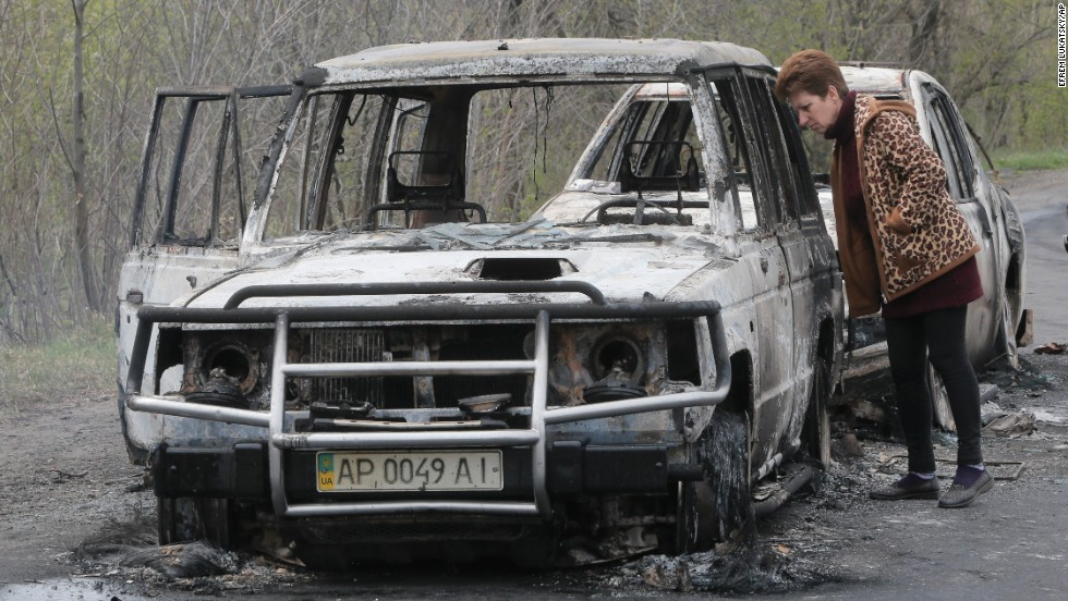 A resident inspects burnt-out cars at a roadblock on April 20.