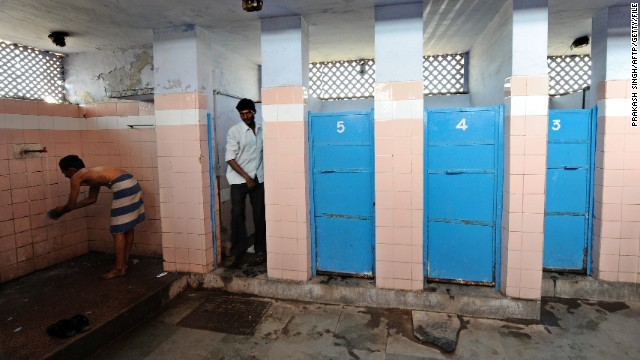 File photo: A Indian man washes as another comes out of a toilet in a toilet complex run by an NGO Sulabh International at railway station in New Delhi in 2011.