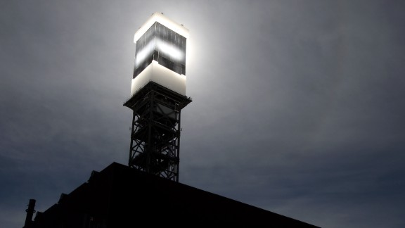 Sunlight from mirrors is reflected onto a solar receiver and boiler. Water is heated to produce steam to power turbines.