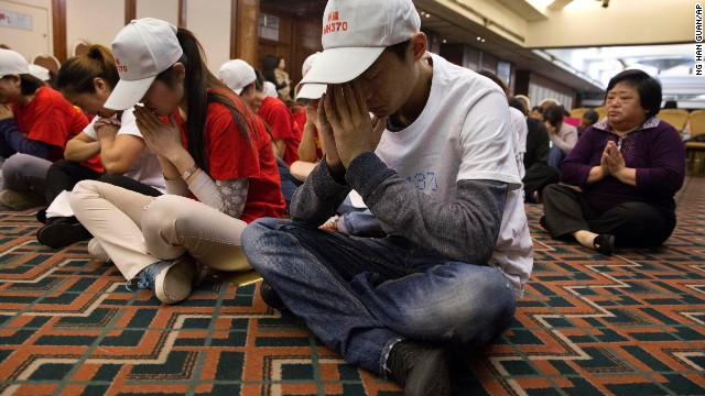 Relatives of Chinese passengers on board the Malaysia Airlines Flight 370 pray at a hotel conference room in Beijing, China, Friday, April 18, 2014. A robotic submarine headed back down into the depths of the Indian Ocean on Friday to scour the seafloor for any trace of the missing Malaysian jet one month after the search began off Australia's west coast, as data from the sub's previous missions turned up no evidence of the plane.(AP Photo/Ng Han Guan)
