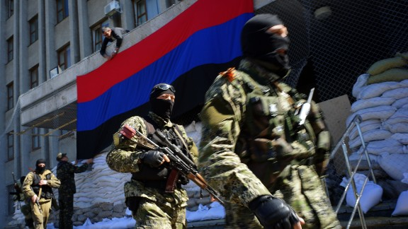 Caption:A pro-Russia activist hangs a flag of the so-called 'People's Republic of Donetsk' on the regional administration building seized by separatists as armed men in military fatigues guard the premises in the eastern Ukrainian city of Slavyansk on April 21, 2014. US Vice President Joe Biden will begin a two-day visit to Ukraine, hours after a fragile Easter truce was shattered and pro-Kremlin rebels in the country's east appealed for help from Russian 'peacekeepers'. AFP PHOTO / GENYA SAVILOV (Photo credit should read GENYA SAVILOV/AFP/Getty Images)