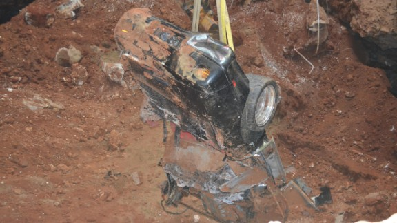 """As a crane pulled the Spyder from underground, museum officials said it became apparent it was among the worst damaged. A large boulder was found lodged in the Spyder's cabin, according to the museum website. At the time of the sinkhole collapse, the car was on display with its hood open. The fall snapped the hood off, <a href=""""http://corvettemuseum.blogspot.com/2014/04/zr-1-spyder-recovered-from-sinkhole.html"""" target=""""_blank"""" target=""""_blank"""">the website said</a>."""