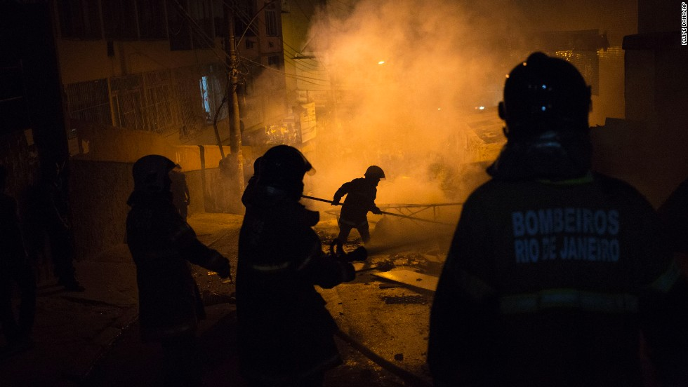Firefighters put out a burning barricade during clashes.