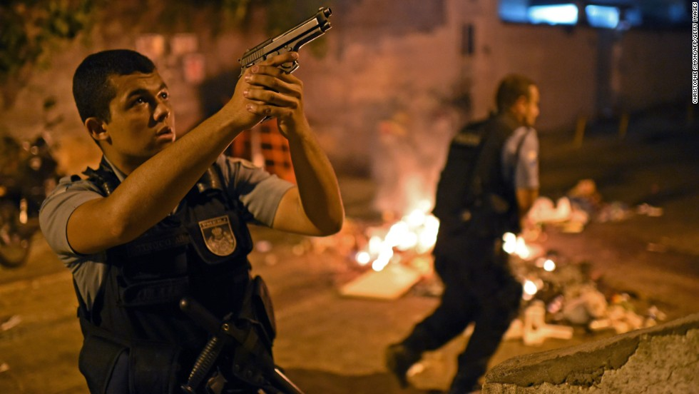 A police officer points his weapon during the protests.