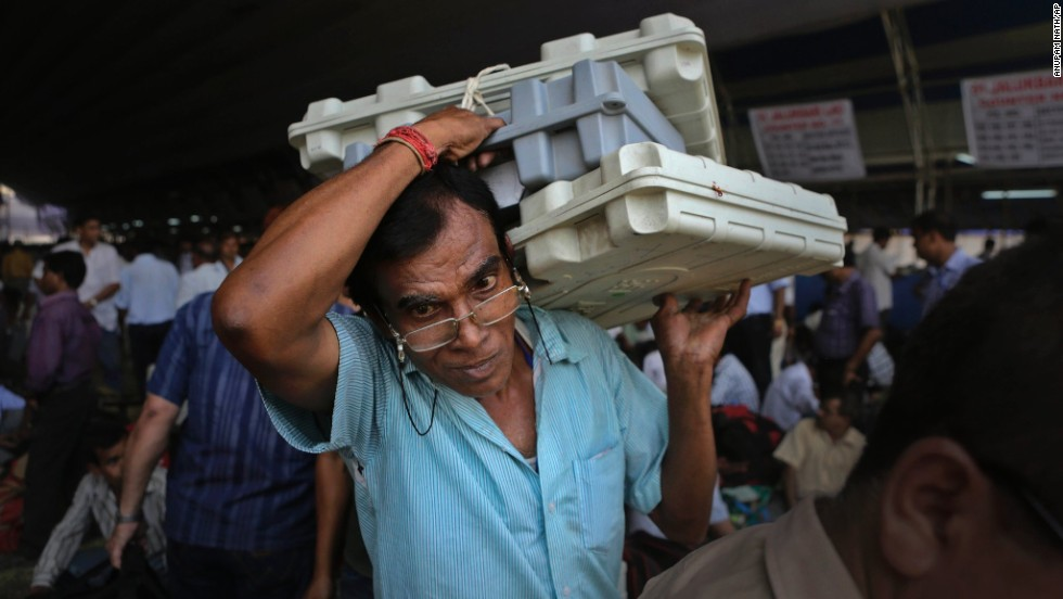 A polling official carries electronic voting machines at a distribution center in Gauhati, India, on Wednesday, April 23.