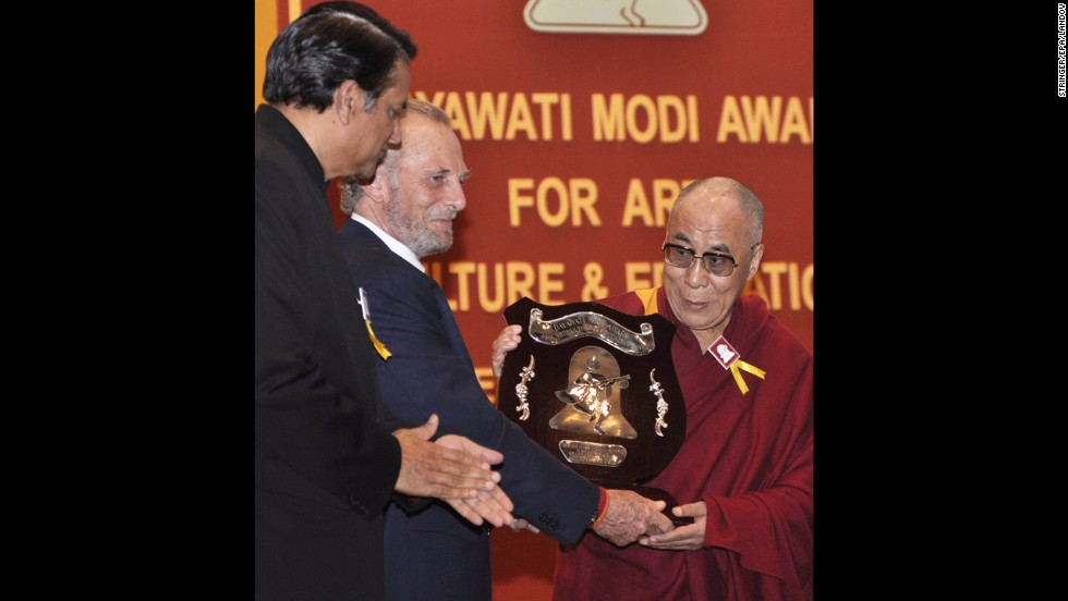 The Dalai Lama is presented with the Dayawati Modi Award for 2011 by Shand, center, in New Delhi on December 2, 2011. SK Modi, left, president of the Dayawati Modi Foundation, looks on.