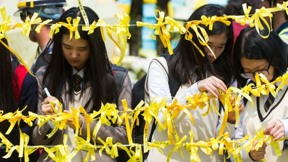 Caption:Schoolchildren tie yellow ribbons symbolising hope for the safe return of missing passengers on the